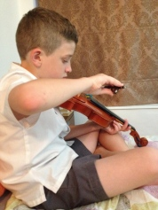 Kiddo with haircut practicing violin.